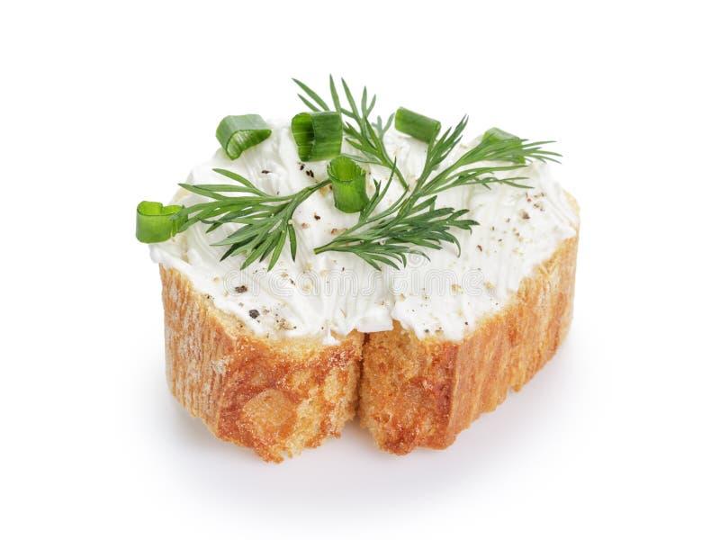 Rebanada crujiente del baguette con el queso cremoso y las hierbas imagen de archivo libre de regalías
