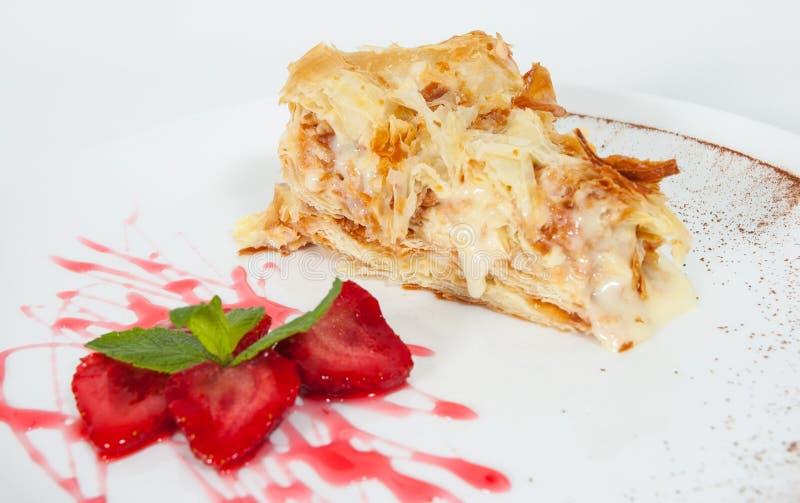 Rebanada de adornado con la torta de napoleon de la fresa, servida en la placa blanca fotografía de archivo