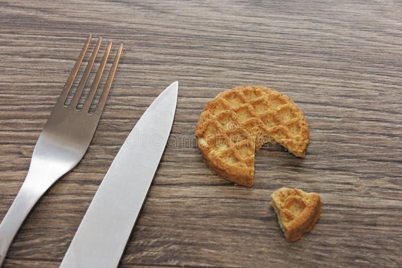 Rebanada de galletas de cereales dietéticos sobre fondo de madera oscura con tenedor y cuchillo fotografía de archivo