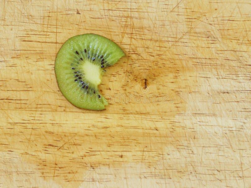 Rebanada de la fruta de kiwi con una mordedura en ella imagen de archivo