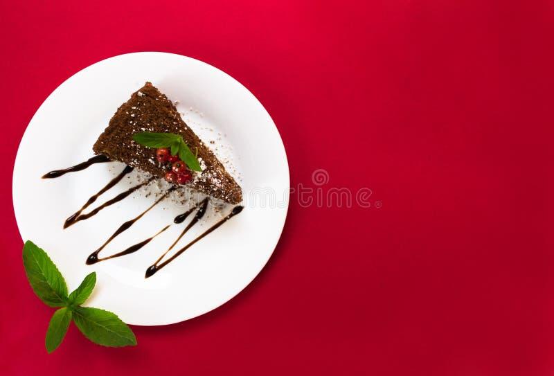Rebanada de la torta de chocolate con las bayas y las hojas de la menta en una placa, opinión superior sobre un fondo rojo Copie  imagenes de archivo