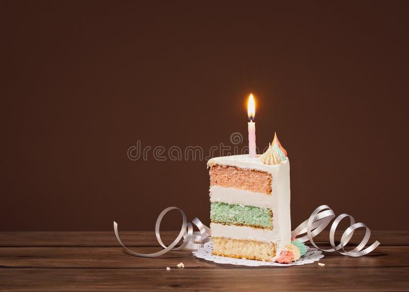 Rebanada de la torta de cumpleaños con la vela foto de archivo libre de regalías