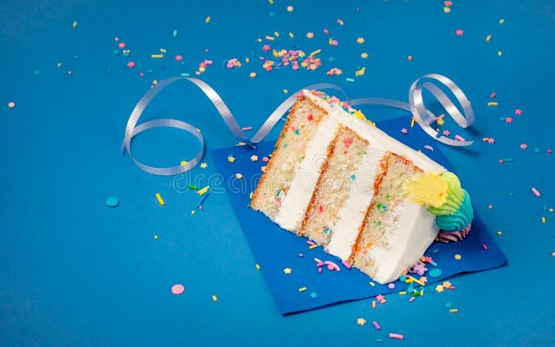 Rebanada de la torta de cumpleaños en fondo azul fotos de archivo