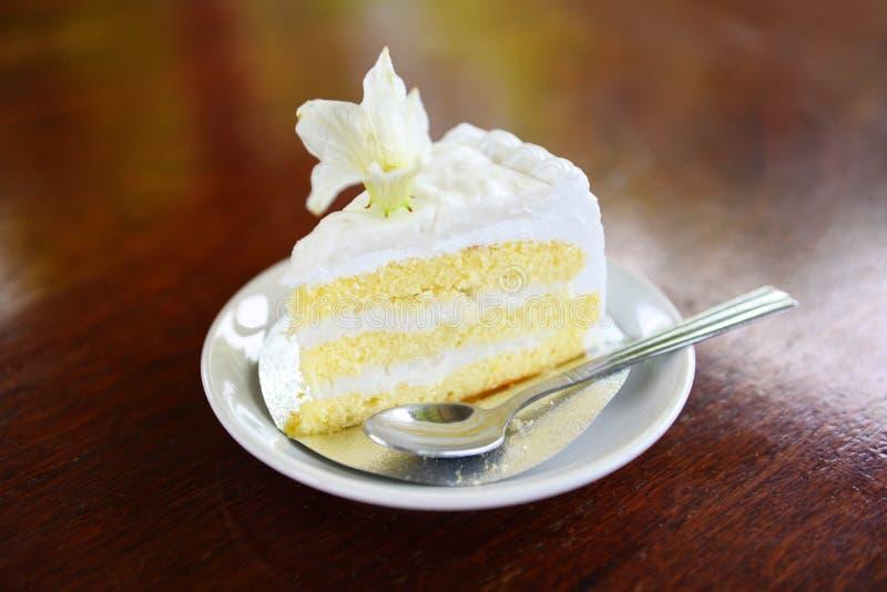 Rebanada de la torta en el palte blanco con la flor en fondo de madera de la tabla - torta y cuchara deliciosas de coco imagenes de archivo