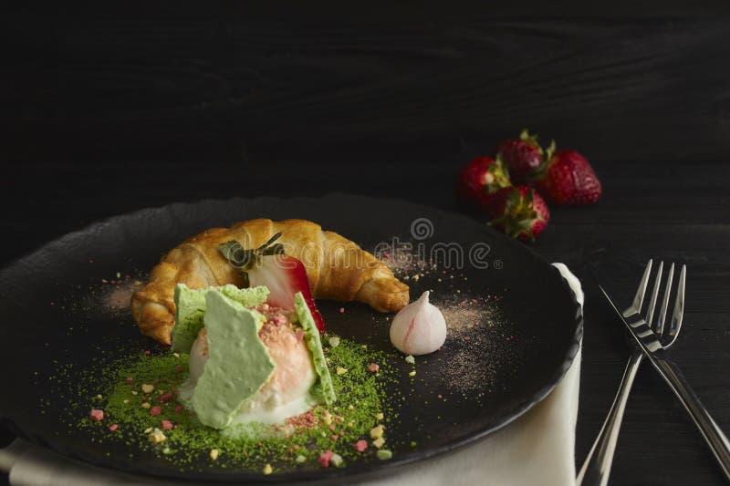 Rebanada de milhojas de manzana con una cucharada del helado de vainilla en una placa negra, en una tabla negra de madera, adorna foto de archivo libre de regalías
