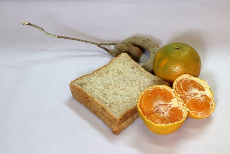 Rebanada de pan con la naranja y la naranja pelada y de tamarindo aislado en el fondo blanco imágenes de archivo libres de regalías