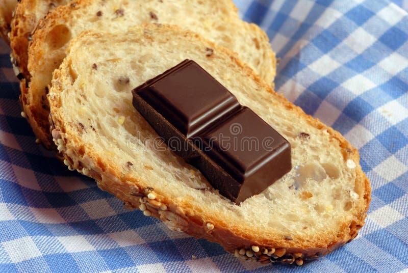 Rebanada de pan con los cuadrados del chocolate foto de archivo