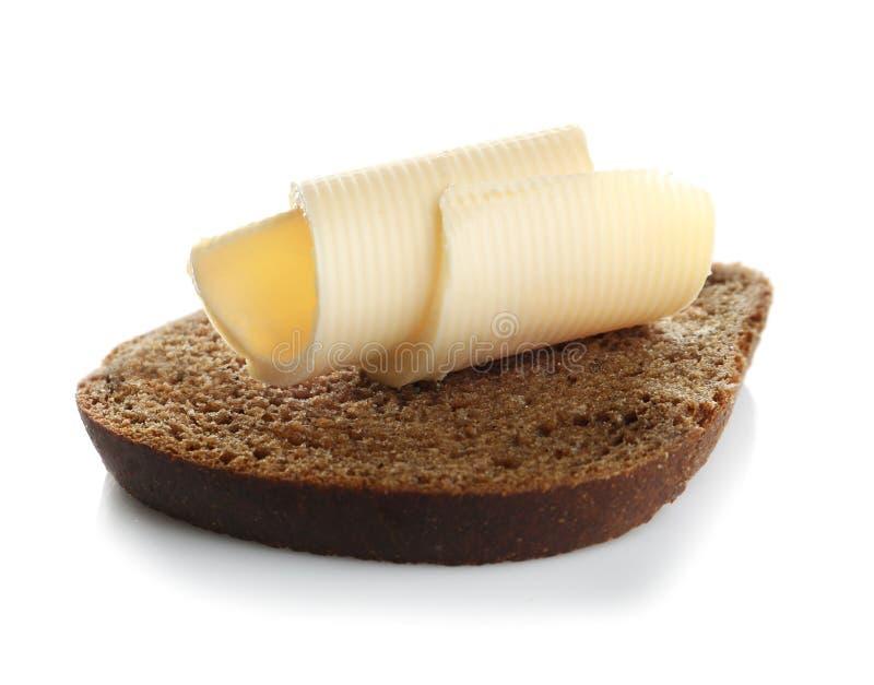 Rebanada de pan con los rizos de la mantequilla imagen de archivo