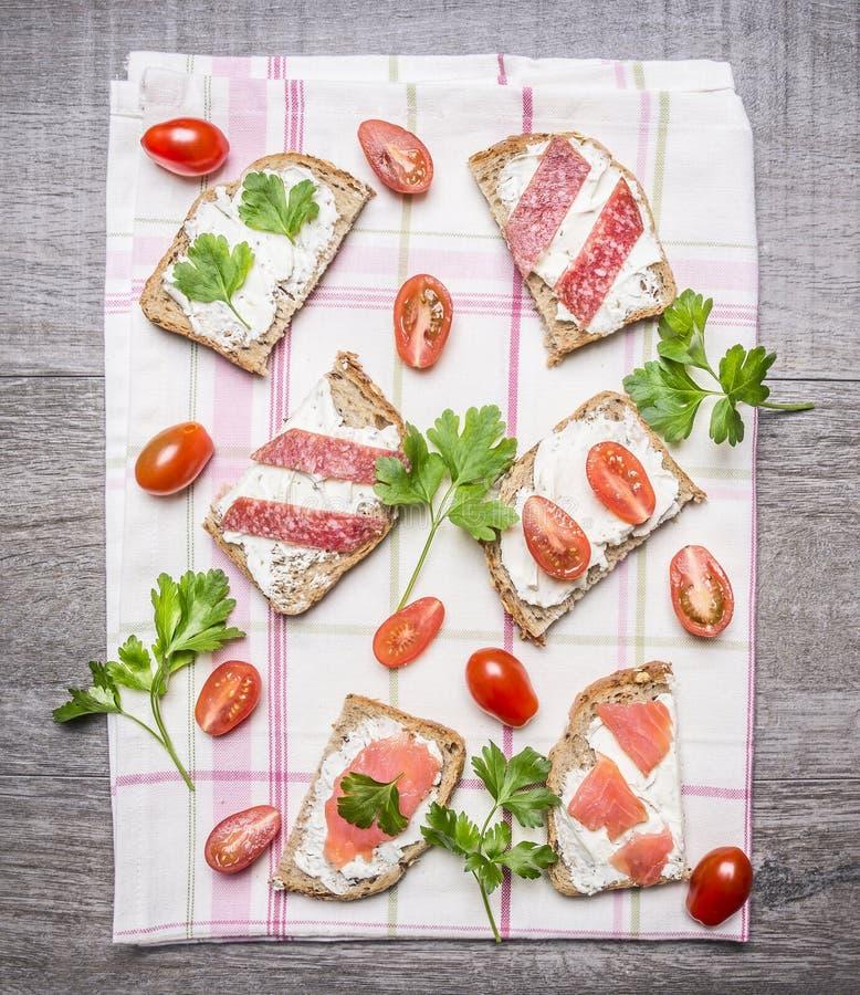 Rebanada de pan de centeno fresco con el queso cremoso con los pescados, los tomates de cereza y el perejil rojos del salami en u imagenes de archivo