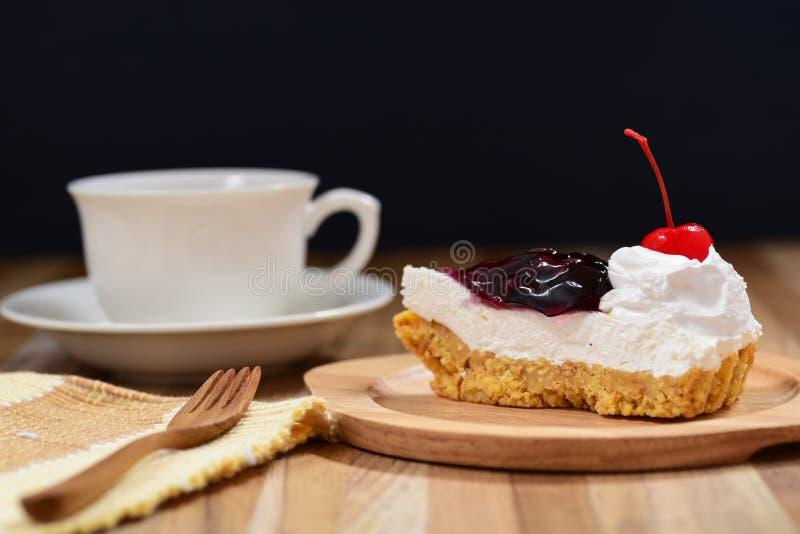 Rebanada de pastel de queso del arándano en la tabla de madera imagen de archivo