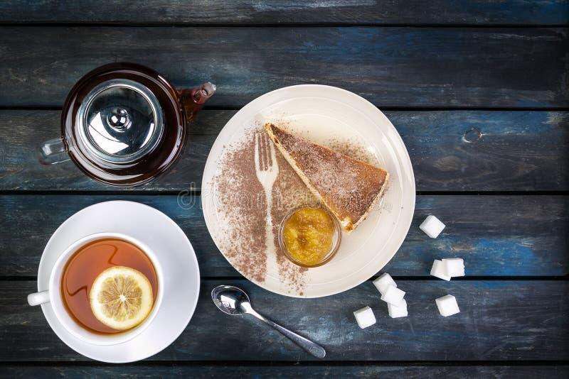 Rebanada de pastel de queso con la caldera del atasco y de té con el limón en un fondo de madera coloreado Visión superior imagen de archivo libre de regalías