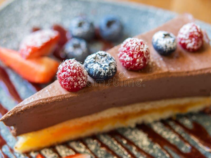 Rebanada de pastel de queso del chocolate con las fresas, los arándanos y las frambuesas en la placa azul, sobre la visión sobr imagen de archivo libre de regalías