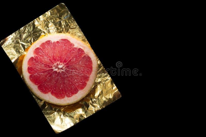Rebanada de pomelo en una hoja amarilla foto de archivo libre de regalías