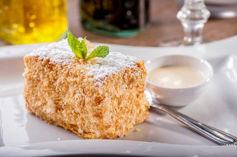 Rebanada de primer de la torta de Napoleon en el plato blanco con la hoja de la menta y el cuenco de salsa cremosa fotografía de archivo libre de regalías
