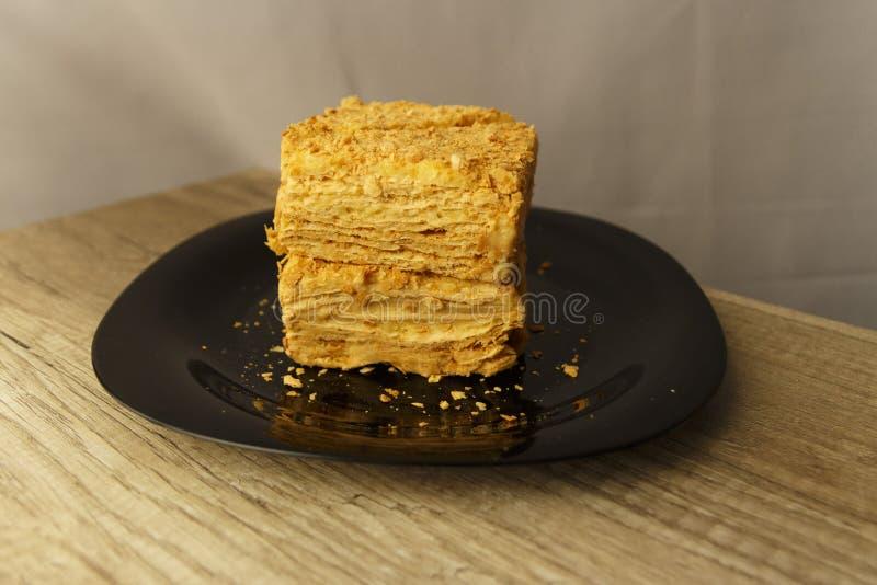 Rebanada de torta anaranjada en la placa negra en la tabla de madera, fondo de la comida imagen de archivo
