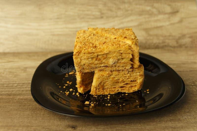 Rebanada de torta anaranjada en la placa negra en la tabla de madera, fondo de la comida foto de archivo