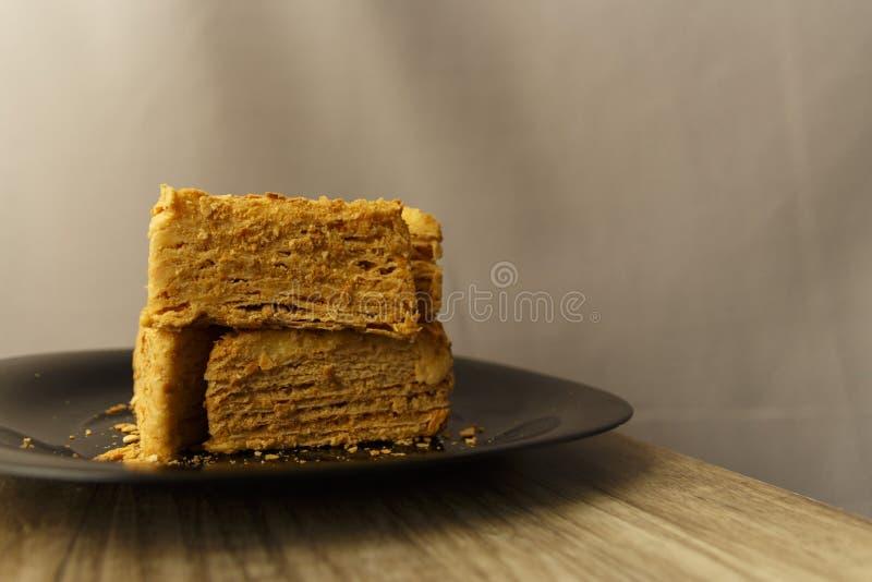 Rebanada de torta anaranjada en la placa negra en la tabla de madera, fondo de la comida fotografía de archivo