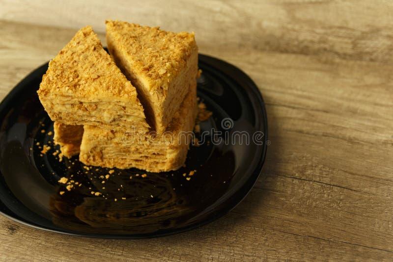 Rebanada de torta anaranjada en la placa negra en la tabla de madera, fondo de la comida imagen de archivo libre de regalías