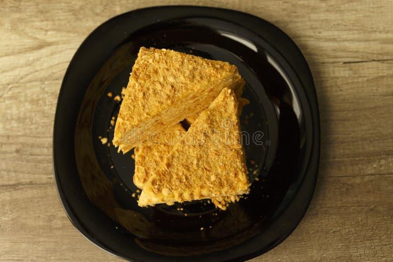 Rebanada de torta anaranjada en la placa negra en la tabla de madera, fondo de la comida imágenes de archivo libres de regalías