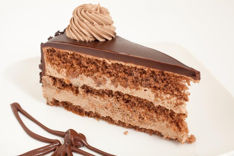 Rebanada de torta de chocolate con la decoración en la placa blanca fotografía de archivo libre de regalías