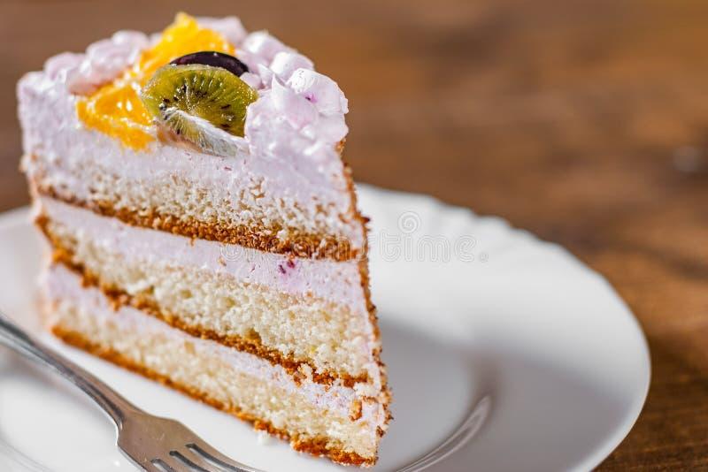 Rebanada de torta de cumpleaños acodada con crema con la fruta en una placa en de madera foto de archivo libre de regalías