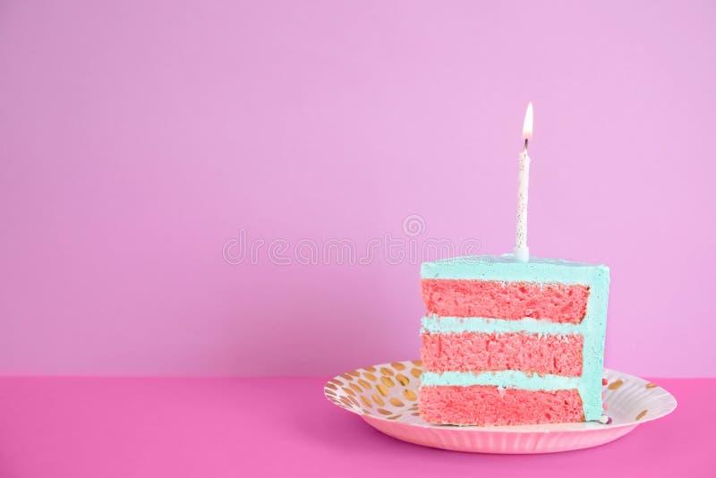 Rebanada de torta de cumpleaños deliciosa fresca con la vela en la tabla contra fondo del color fotografía de archivo