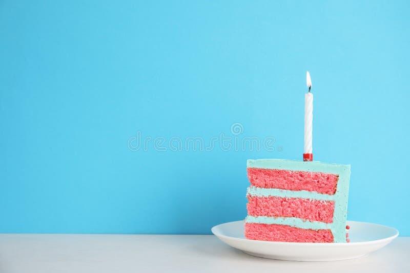 Rebanada de torta de cumpleaños deliciosa fresca con la vela en la tabla contra fondo del color imagen de archivo