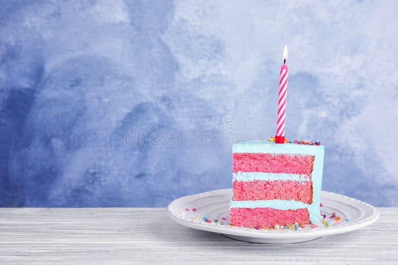 Rebanada de torta de cumpleaños deliciosa fresca con la vela en la tabla contra fondo del color imágenes de archivo libres de regalías