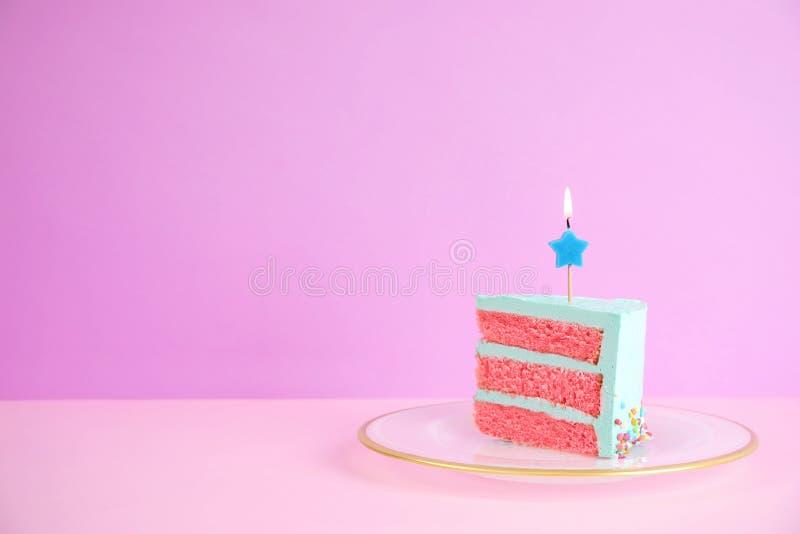 Rebanada de torta de cumpleaños deliciosa fresca con la vela en la tabla contra fondo del color fotos de archivo libres de regalías