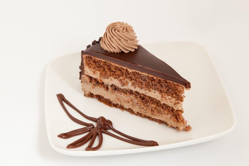 Rebanada de torta de chocolate con la decoración en la placa blanca fotos de archivo