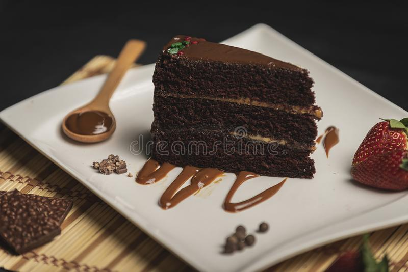Rebanada de torta del chococlate con caramelo en la placa blanca sobre la tabla de madera fotografía de archivo libre de regalías