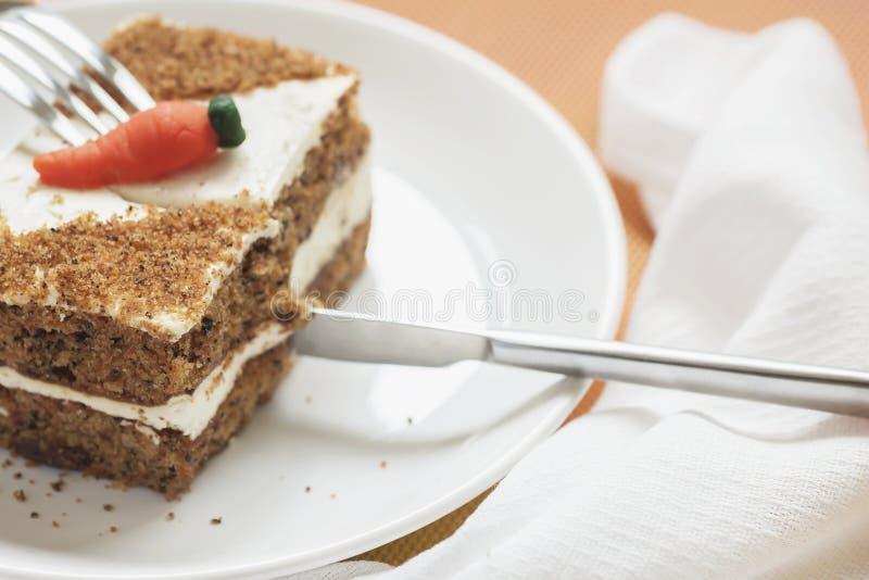 Rebanada de torta de zanahoria hecha casera, placa blanca, servilleta El cuchillo corta un pedazo apetitoso Comida sana dulce del foto de archivo libre de regalías