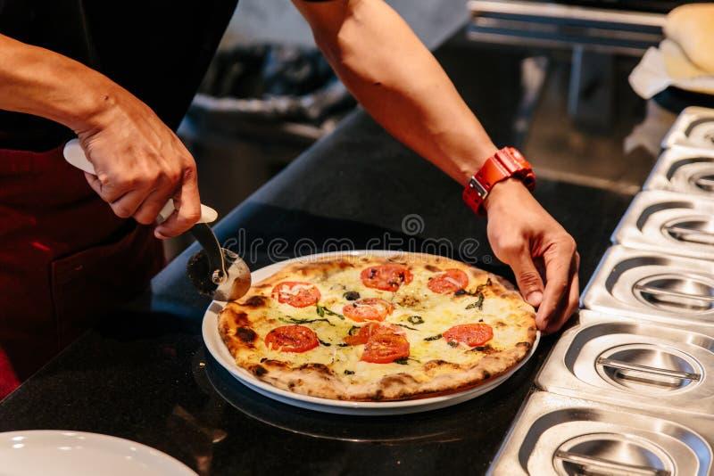 Rebanada del cocinero un Caprese caliente Bianca Pizza antes de la porci?n Los ingredientes son aceite de la mozzarella, del parm imagenes de archivo