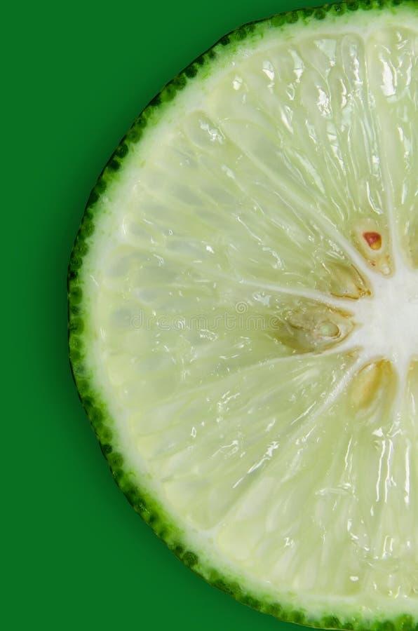 Rebanada del limón y de la cal y agrios frescos en fondo verde imagenes de archivo
