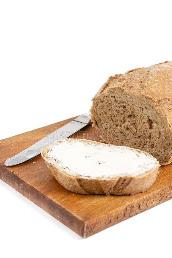 Rebanada del pan con mantequilla en el tablero de madera imagenes de archivo