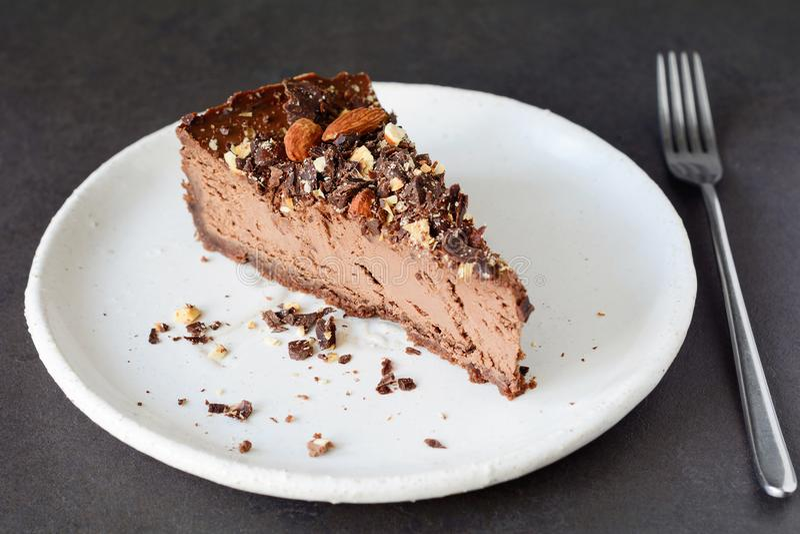 Rebanada del pastel de queso del chocolate en la placa blanca imagen de archivo