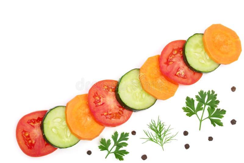 Rebanada del tomate, del pepino y de la zanahoria con las especias aisladas en el fondo blanco con el espacio de la copia para su fotografía de archivo
