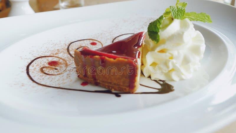 Rebanada deliciosa de hermoso del pastel de queso servida en una placa blanca con crema y la hoja de la menta fotografía de archivo libre de regalías