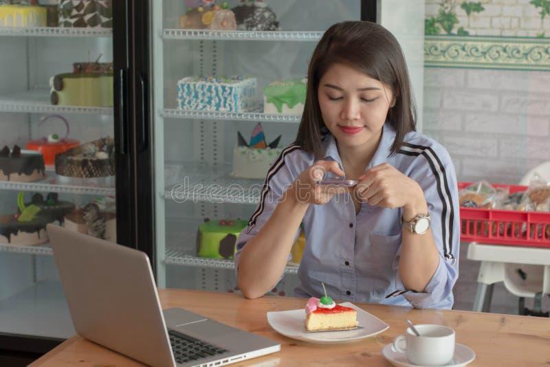 Rebanada femenina asi?tica atractiva de la imagen que toma de torta de la fresa con smartphone a cargar en medios sociales fotos de archivo
