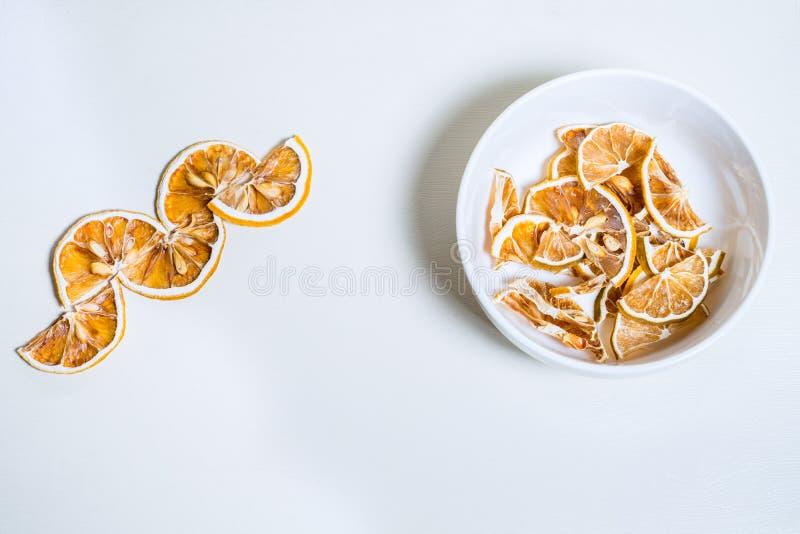 Rebanada secada del limón apilada en el cuenco blanco junto fotos de archivo