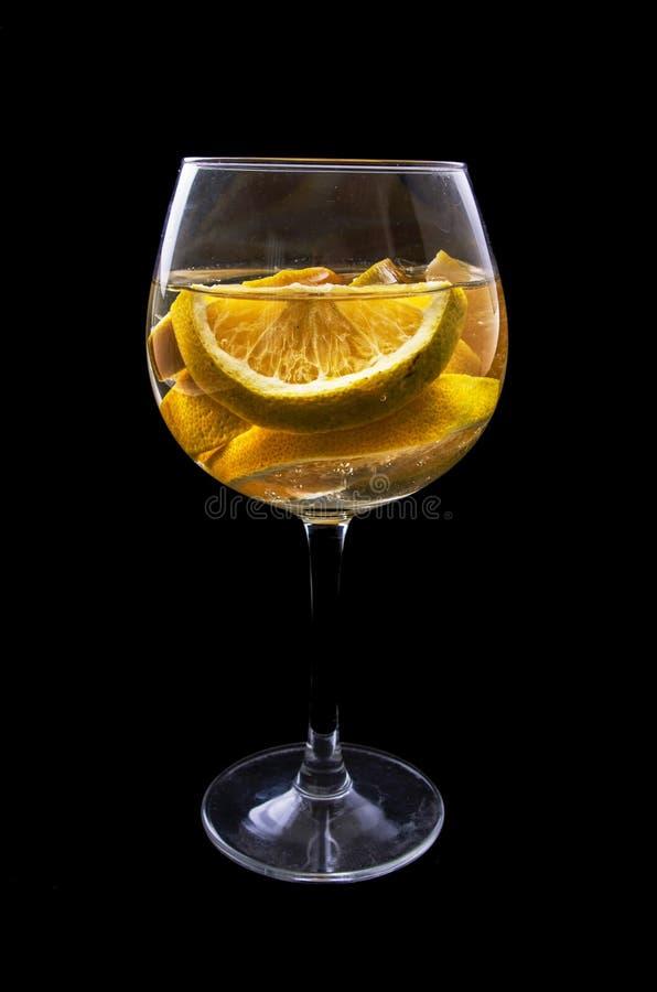 Rebanadas anaranjadas sobre un vidrio en el vino con oscuridad fotografía de archivo