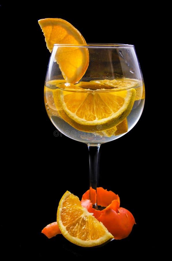 Rebanadas anaranjadas sobre un vidrio en el vino con oscuridad foto de archivo
