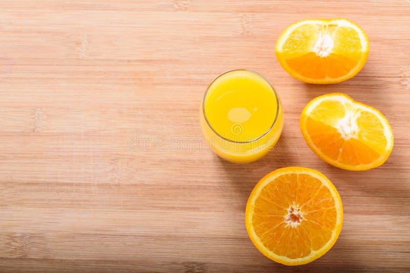 Rebanadas anaranjadas y un vidrio con el zumo de naranja imagen de archivo