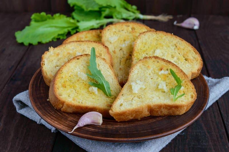 Rebanadas asadas a la parrilla de pan blanco con ajo e hierbas en fondo de madera oscuro imagen de archivo