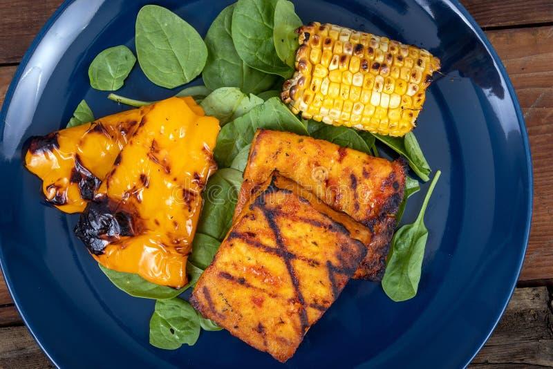 Rebanadas asadas a la parrilla deliciosas del queso de soja con maíz y paprika amarillo imagenes de archivo