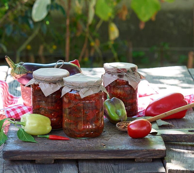 Rebanadas conservadas de la berenjena en salsa vegetal picante en los tarros de cristal imagen de archivo