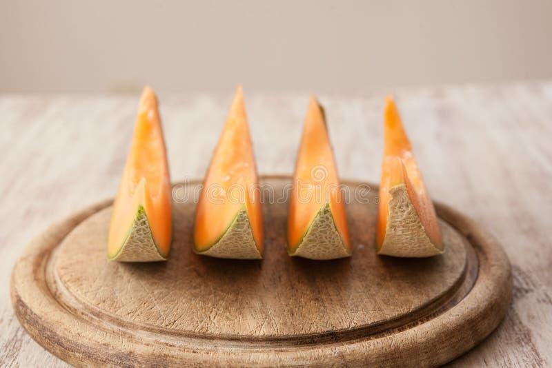 Rebanadas de cantalupo en la tabla de cortar de madera en fila fotografía de archivo