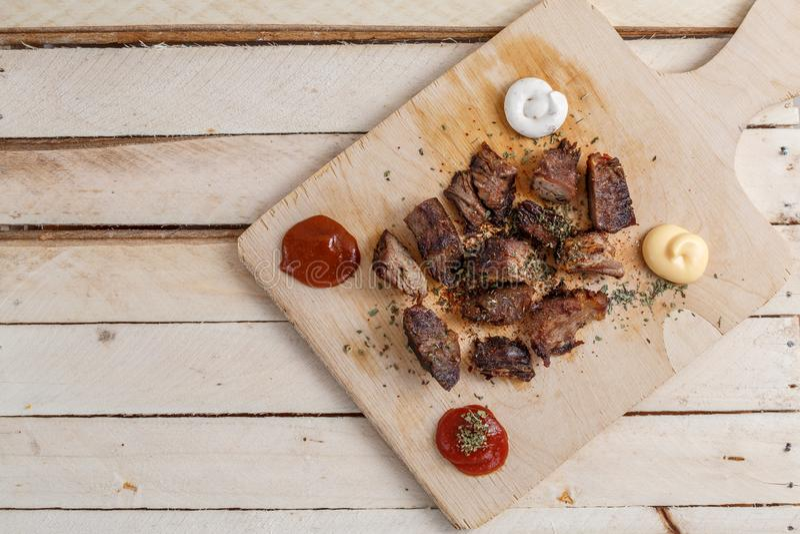 Rebanadas de carne de vaca frita en un cuenco de madera con diversos tipos de salsas en un fondo de madera ligero foto de archivo
