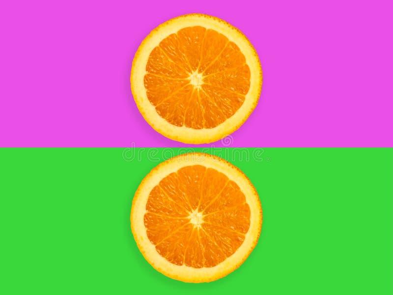 Rebanadas de fruta anaranjada aisladas en el fondo en colores pastel púrpura y verde colorido - imagen minimalistic y creativa mo imagenes de archivo