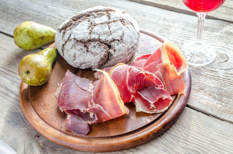 Rebanadas de jamón italiano en el tablero de madera fotografía de archivo libre de regalías